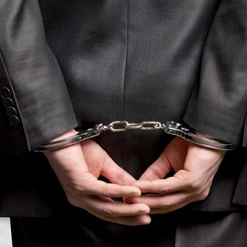 A Man in a Business Suit Is Handcuffed.
