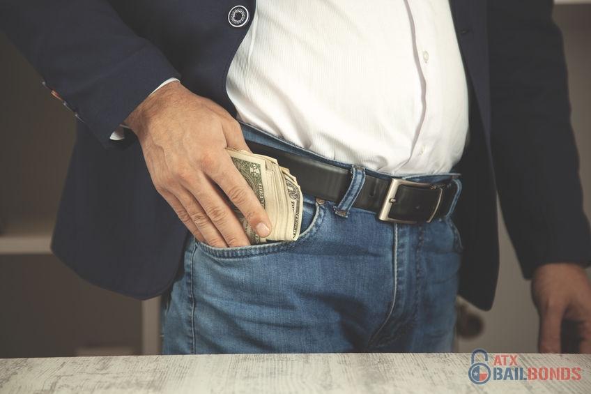 Businessman's Hand Putting Money in Pocket